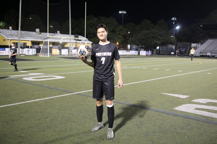 Holding a ball, sophomore Hayden Judge poses for a photo. Hayden started playing soccer at the age of three.