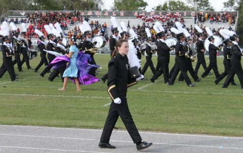 Shako in hand, drum major junior Ainsley Neil walks on the track. The drum majors use stands so the band members can see them keep time and conduct.