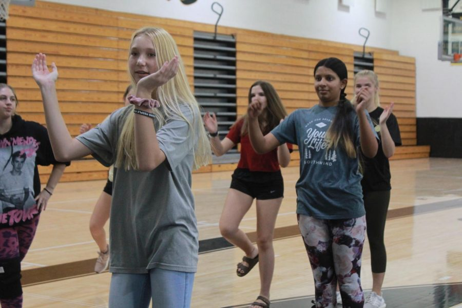 Demonstrating a move, junior Gabby Fasulo helps coach cheerleading. Fasulo has been in the Special Olympics club since her freshman year.