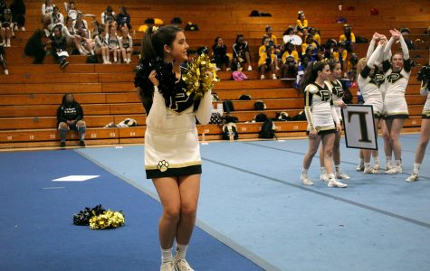 Pom-poms in hand, freshman Bella Guerra chants with the rest of her team at the cheer competition held in the Robinson gymnasium. The girls competed against other Hillsborough county teams, ranked based on difficulty and execution.