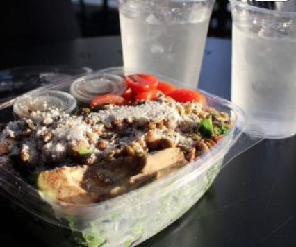 Served in a to-go container, the Farmacy's Herb Roasted Kale Caesar Salad is presented alongside two cups of ice water. The salad was comprised of garlic roasted chickpeas, heirloom tomatoes and avocado atop a mix of kale and Caesar dressing.