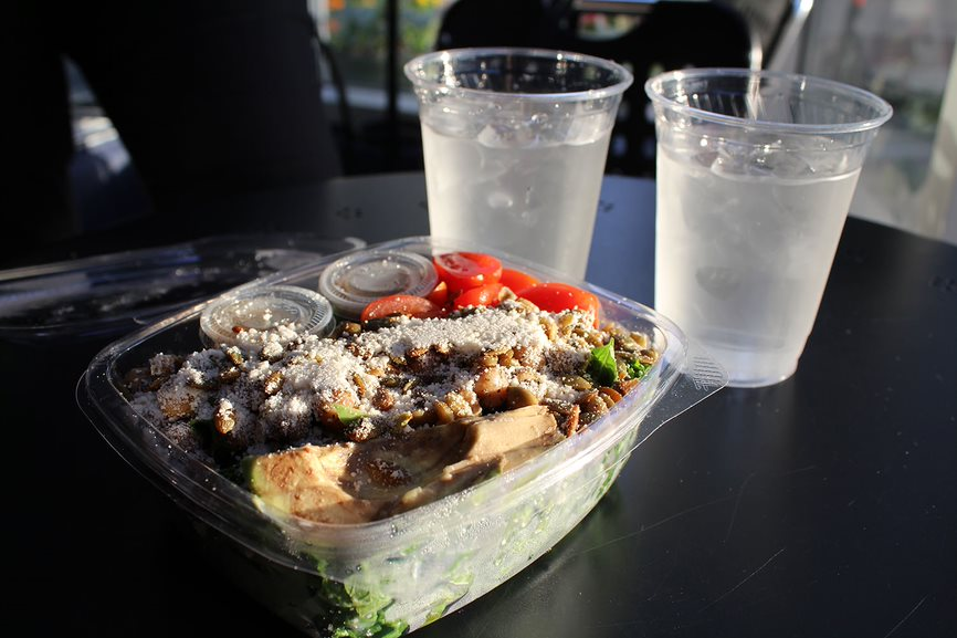 Served+in+a+to-go+container%2C+the+Farmacy%E2%80%99s+Herb+Roasted+Kale+Caesar+Salad+is+presented+alongside+two+cups+of+ice+water.+The+salad+was+comprised+of+garlic+roasted+chickpeas%2C+heirloom+tomatoes+and+avocado+atop+a+mix+of+kale+and+Caesar+dressing.