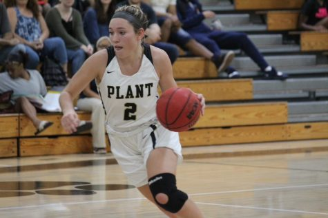 With a knee brace on, senior Honor Culpepper dribbles the ball down the court. The varsity girls basketball team ended the season ranked tenth in the state.