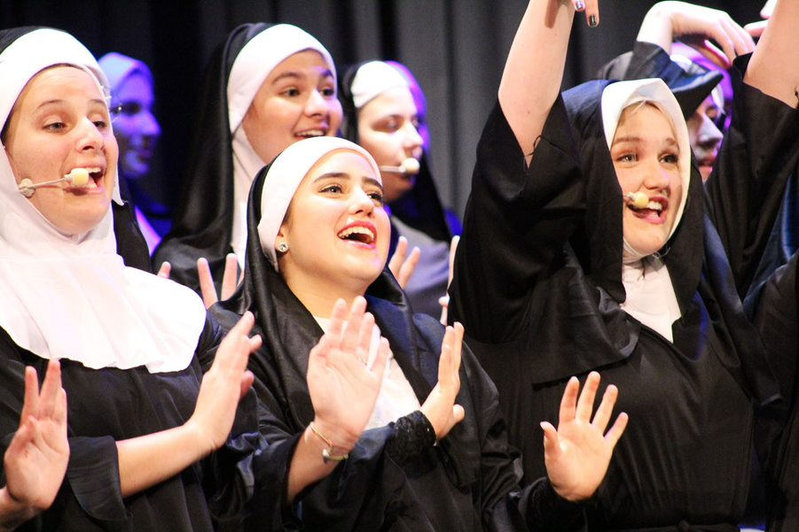 "Hands raised, senior Natalie Ulm, junior Neena Moradiellos and sophomore Sydney Goldberg sing with the varsity women's chorus Feb. 14 in the auditorium. The varsity women's chorus sang a selection of songs from the musical ""Sister Act."""