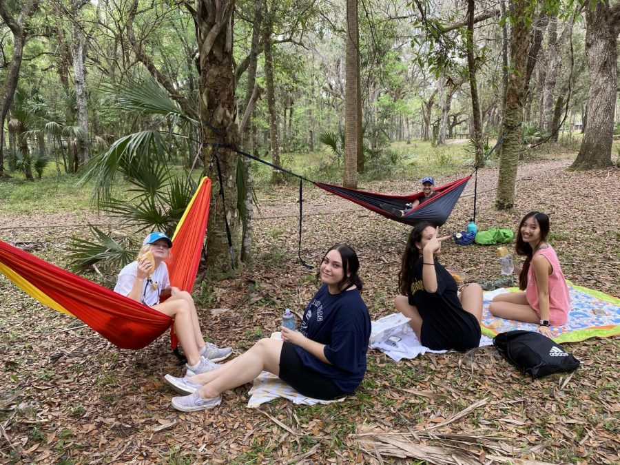 At lunch, students sit with Margaret Drumsta while on blankets and hammocks. Drumsta came prepared with the hammock because of her many times visiting the site.