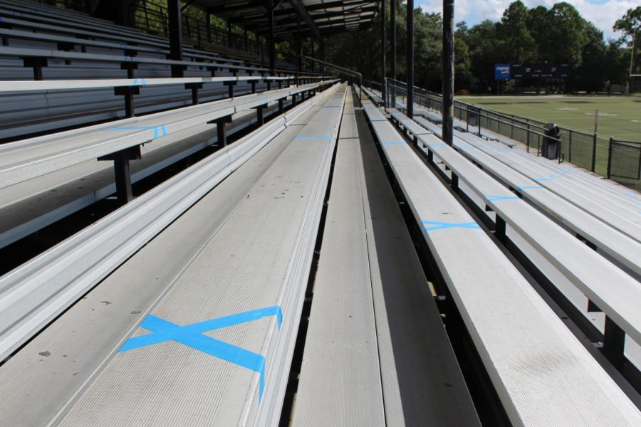 Walking up the bleachers blue masking tape X's mark where spectators will sit. Each group of four spectators submitted by the student athlete will sit between the X's.