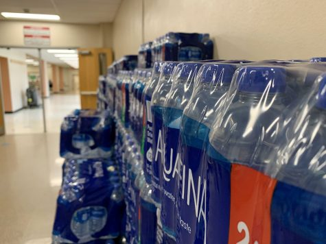 Stacked three layers high, packages of plastic water bottles line the hallway near the cafeteria. The school began providing plastic water bottles this year to compensate for water fountains being shut off to prevent coronavirus spread.
