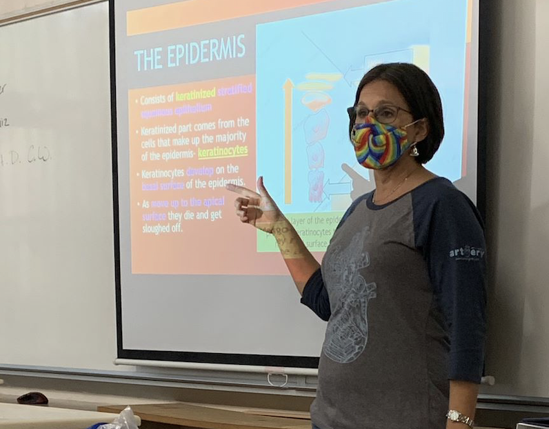 Lecturing in class, Christie Rainbeau explains about the different layers of skin. After 10 years, Friday, Oct. 9 was Rainbeau's last day teaching at Plant High School.