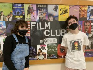 Standing next to the film club board in main hall, co-presidents Alexa Semmelmann and Owen Felton talk about their time with the film club. Film club consists of monthly meetings to talk about influential films.