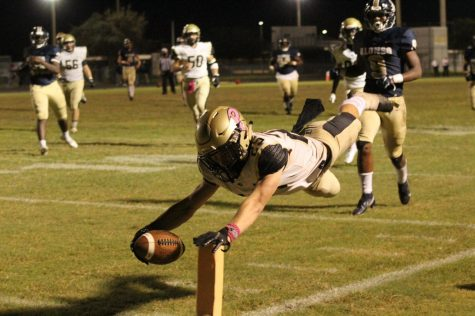 Holding out the ball, junior wide receiver Peter Essad reaches for the end zone. The varsity football team defeated Alonso High School on Friday, Oct. 30 giving them their second win of the season.