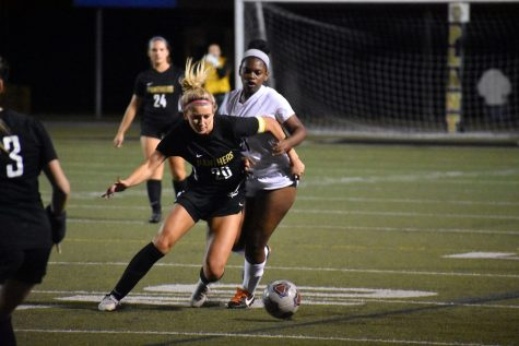 Defending the ball, senior left back Claire Rain carries the ball downfield to the Wharton goal, Nov. 17 at Dad's Stadium. The team defeated Wharton 3-0.