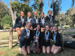 Posing with their state championship trophy, the girls cross country team stands together at Apalachee Regional Park in Tallahassee, FL on Nov. 10. They brought home their 12th state title under the coaching of Roy Harrison.