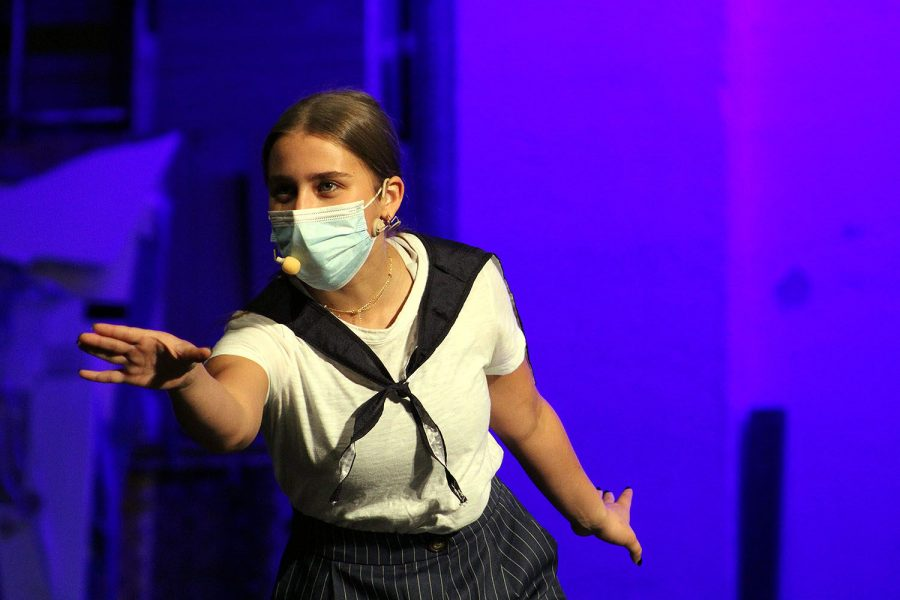 "Singing underneath a mask, senior Natalie Yale looks out into the audience during ""Anything Goes."" The concert will be livestreamed online due to the pandemic."