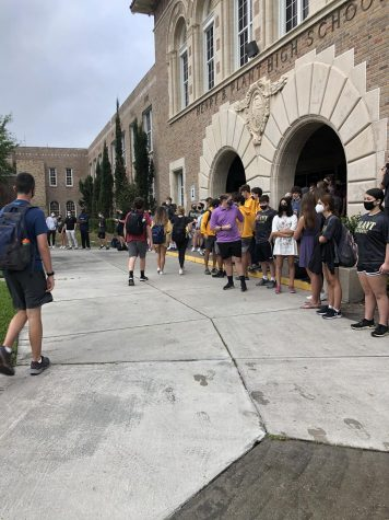 Gathered at the front of the school, students hold a moment of silence for junior Charlie Carl who passed away March 18. Students were asked to wear purple, the representative color for epilepsy awareness.