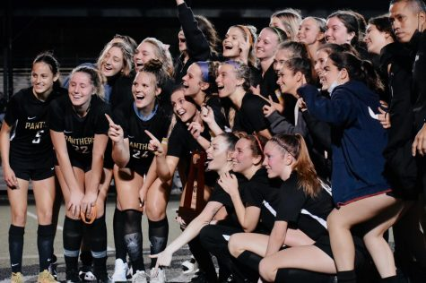 Huddled around the trophy, the girls soccer team smiles for a picture after defeating Palm Harbor University 1-0 on Feb. 9. The girls won the FHSAA Girls Soccer District 7A-7 champions allowing them to advance on to regionals.