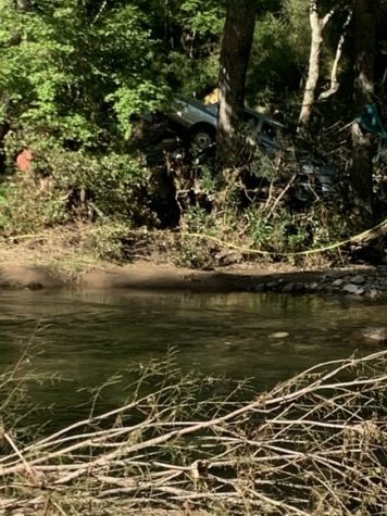 This is a photo of a car stuck in between the trees of a mountain in Haywood County, NC. This would have been because of the detrimental floods that moved it to this distorted position shown.